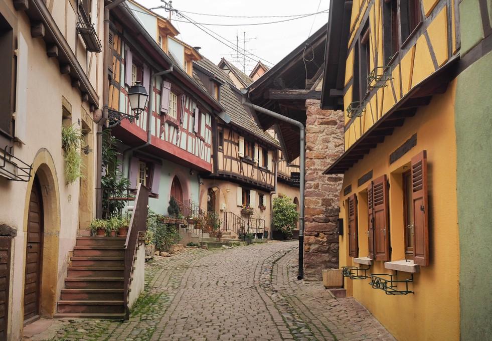 Fachwerkhäuser entlang einer historischen Seitenstraße mit Kopfsteinpflaster in Eguisheim. (#5)